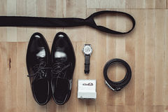 Close up of modern groom accessories. wedding rings, black necktie, leather shoes and watch. On the wooden floor. Selective focus Stock Image