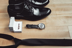 Close up of modern groom accessories. wedding rings, black necktie, leather shoes and watch. On the wooden floor. Selective focus Stock Images