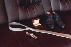 Close up of modern groom accessories. wedding rings in a brown wooden box, necktie, leather shoes and watch. On a brown sofa. Selective focus Stock Image