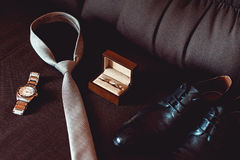 Close up of modern groom accessories. wedding rings in a brown wooden box, necktie, leather shoes and watch. On a brown sofa. Selective focus Stock Photos