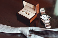 Close up of modern groom accessories. wedding rings in a brown wooden box, necktie and watch Royalty Free Stock Photo