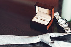 Close up of modern groom accessories. wedding rings in a brown wooden box, necktie and watch. Selective focus Royalty Free Stock Photo