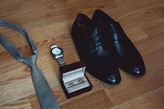 Close up of modern groom accessories. wedding rings, gray necktie, leather shoes and watch. On the wooden floor. Selective focus Royalty Free Stock Image