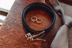 Close up of modern groom accessories. wedding rings, necktie, leather shoes and belt Royalty Free Stock Images
