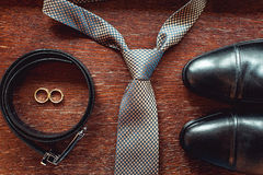 Close up of modern groom accessories. wedding rings, necktie, leather shoes and belt Stock Photos