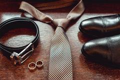 Close up of modern groom accessories. wedding rings, necktie, leather shoes and belt Royalty Free Stock Photos