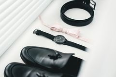 Close up of modern man accessories. beige bow tie, black leather shoes, belt and watch. Close up of modern man accessories Stock Photos