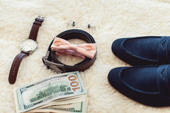Close up of modern man accessories. Biege bowtie, leather shoes, belt, watch, cufflinks, money and wedding rings. Formal style of wearing Royalty Free Stock Images