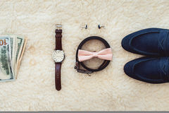 Close up of modern man accessories. Biege bowtie, leather shoes, belt, watch, cufflinks, money and wedding rings. Formal style of wearing. look from above Royalty Free Stock Image