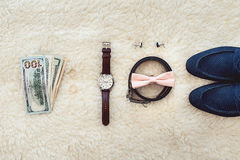 Close up of modern man accessories. Biege bowtie, leather shoes, belt, watch, cufflinks, money and wedding rings. Formal style of wearing. look from above Royalty Free Stock Images