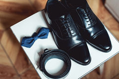 Close up of modern man accessories. black bowtie, leather shoes, and belt. Close up of modern man accessories. black bowtie, leather shoes, and belt on a square Stock Image