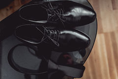 Close up of modern man accessories. black necktie and leather shoes on the black glass table.  Royalty Free Stock Photo