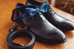 Close up of modern man accessories. Blue bow tie, leather shoes, and belt. Close up of modern man accessories. Blue bow tie, leather shoes, and belt on a wooden Stock Photo