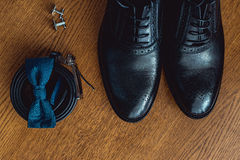 Close up of modern man accessories. Blue bowtie, leather shoes, belt and cufflinks Royalty Free Stock Images