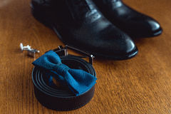 Close up of modern man accessories. Blue bowtie, leather shoes, belt and cufflinks Royalty Free Stock Photos