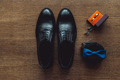 Close up of modern man accessories. Blue bowtie, leather shoes, belt, cufflinks and wedding rings in a orange box Royalty Free Stock Image