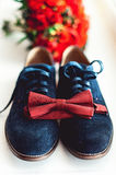 Close up of modern man accessories. Cherry bow tie, blue leather shoest and red wedding bouquet on a carpet. Royalty Free Stock Photos