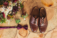 Close up of modern man accessories. purple bow-tie, leather shoes, belt and flower boutonniere on wood chair rustic. Close up of modern man accessories. purple Stock Photos