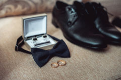 Close up of modern man accessories. wedding rings, black bowtie, leather shoes, belt and cufflinks Royalty Free Stock Photos