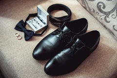 Close up of modern man accessories. wedding rings, black bowtie, leather shoes, belt and cufflinks Royalty Free Stock Photo