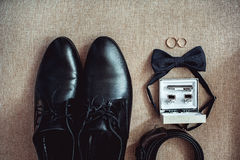 Close up of modern man accessories. wedding rings, black bowtie, leather shoes, belt and cufflinks Royalty Free Stock Image