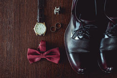 Close up of modern man accessories. wedding rings, cherry bowtie, leather shoes, watch and cufflinks. On the brown wooden table. Selective focus. groom`s Royalty Free Stock Images
