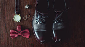 Close up of modern man accessories. wedding rings, cherry bowtie, leather shoes, watch and cufflinks. On the brown wooden table. Selective focus. groom`s Stock Image