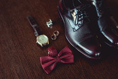 Close up of modern man accessories. wedding rings, cherry bowtie, leather shoes, watch and cufflinks. On the brown wooden table. Selective focus. groom`s Stock Images