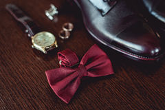 Close up of modern man accessories. wedding rings, cherry bowtie, leather shoes, watch and cufflinks. On the brown wooden table. Selective focus. groom`s Royalty Free Stock Photo