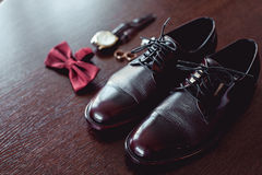 Close up of modern man accessories. wedding rings, cherry bowtie, leather shoes, watch and cufflinks. On the brown wooden table. Selective focus. groom`s Stock Photography