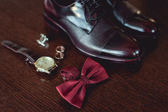 Close up of modern man accessories. wedding rings, cherry bowtie, leather shoes, watch and cufflinks. On the brown wooden table. Selective focus. groom`s Royalty Free Stock Image