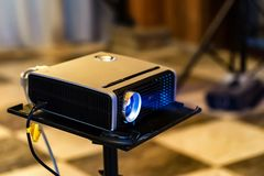 Close up modern projector. Close up modern black multimedia projector standing on black plastic table stock image