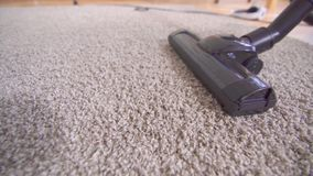 Close up of a vacuum cleaner vacuuming the carpet