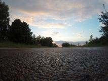 Close up molhado do asfalto no fundo do por do sol, Imagem de Stock