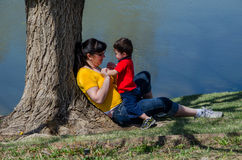 Close up of Mom and child playing by a pond Stock Images