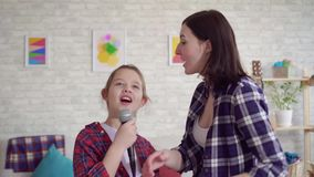 Close up mom and daughter emotionally sing karaoke at home stock video