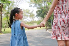 Close-up mom and daughter holding hands in the outdoor nature garden. Back view royalty free stock image