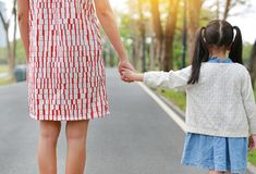 Close-up mom and daughter holding hands in the outdoor nature garden. Back view royalty free stock images