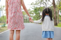Close-up mom and daughter holding hands in the outdoor nature garden. Back view royalty free stock photo