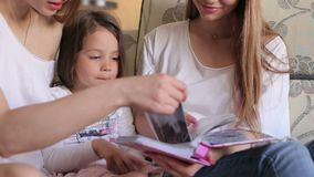 Closeup of mom and daughter and sister watching the photo album at home on couch