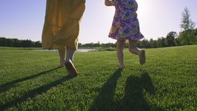 Close-up mom and girl running barefoot on grass stock video