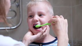 Close-up mother helps to clean the teeth to her little son in the morning. Woman helping son brush his teeth. stock footage