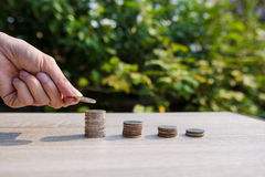 Close up money coins stack. Close up hand putting money coins stack in saving money and growing, concept save money financial Stock Photos