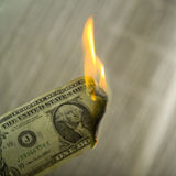 Close up of money on fire. Studio close up of dollar catching fire with newspaper in background Royalty Free Stock Photo
