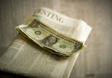 Close up of money on newspaper. Studio close up of dollar bills on newspaper royalty free stock photos
