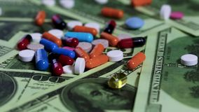 Close-up money and pills of different colour. Drugs on a banknotes. Slow motion video. Close-up green dollars and pills of different colour. Blue, orange, white stock footage