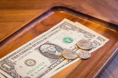 Gratuity money tips, fee charge. Close up money in wooden tray on cafe`s table, dollar banknotes and US coins, modern and minimal style. Concepts for Bill royalty free stock photo