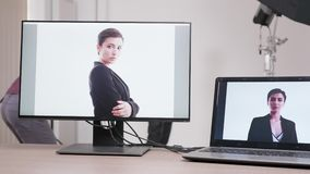 Close up on monitors in professional photo studio set. Photographer is taking pictures tethering of the model and they are appearing on the screen stock video