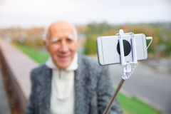 Close-up of a monopod with a telephone in the hands of an elderly man. Royalty Free Stock Photography