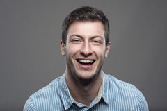Close up moody horizontal portrait of young successful man laughing Royalty Free Stock Image